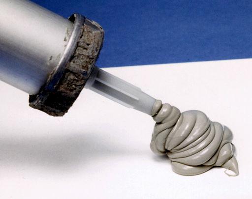 Silikon zum Verfugen wird aus einer Silikonspritze gedrückt und sammelt sich auf einer Fliese