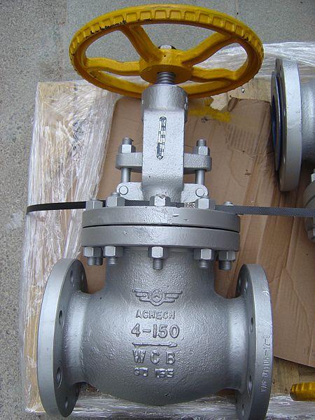 Ein großes Absperrventil mit Handrad liegt auf dem Boden auf einer Holzplatte