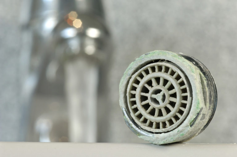 Eine Duschbrause ist total mit Kalk zugesetzt