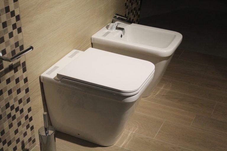 An einer gefliesten Wand hängen zwei unterschiedliche Becken, ein WC und ein Bidet.