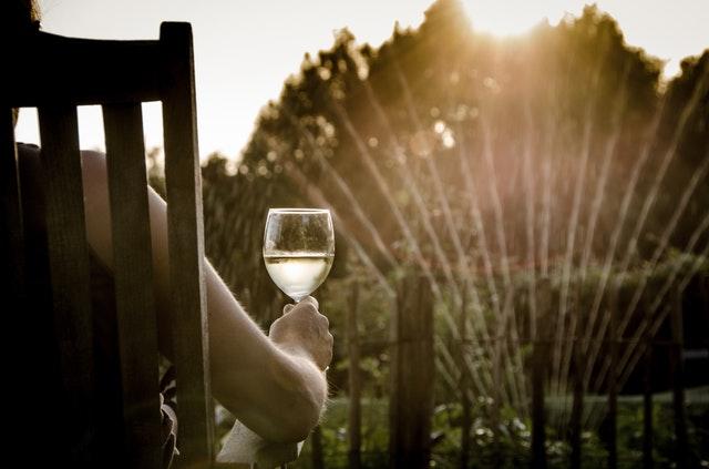 Ein Mensch sitzt mit einem Weinglas in der Hand auf einem Gartenstuhl bei Sonnenuntergang und beobachtet den Rasensprenger.