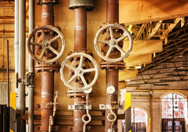 Mehrere alte runde Rohre verlaufen von oben nach unten. Sie besitzen große Stellräder, um sie zu verschließen.