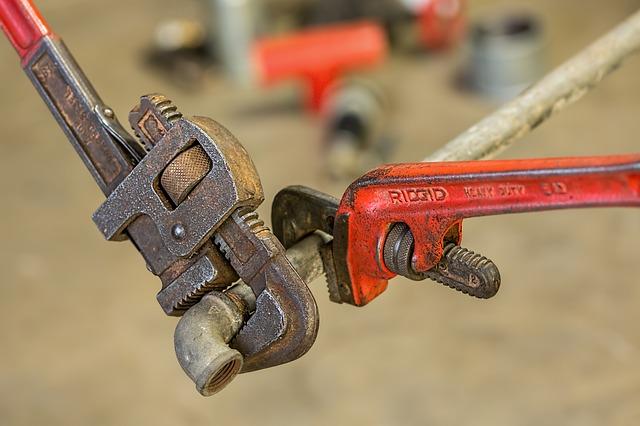 Eine schwarze und eine rote Rohrzange halten ein Rohr fest