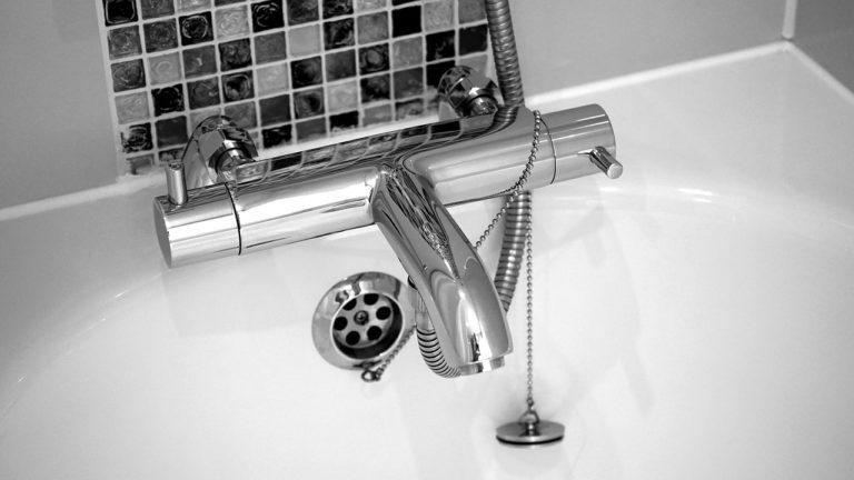 Ein Wasserhahn an einer Badewann, die mit Sanitär-Silikon verfugt ist