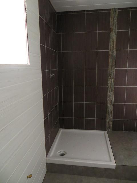 Eine frisch eingebaute quadratische Duschwanne in einem Bad