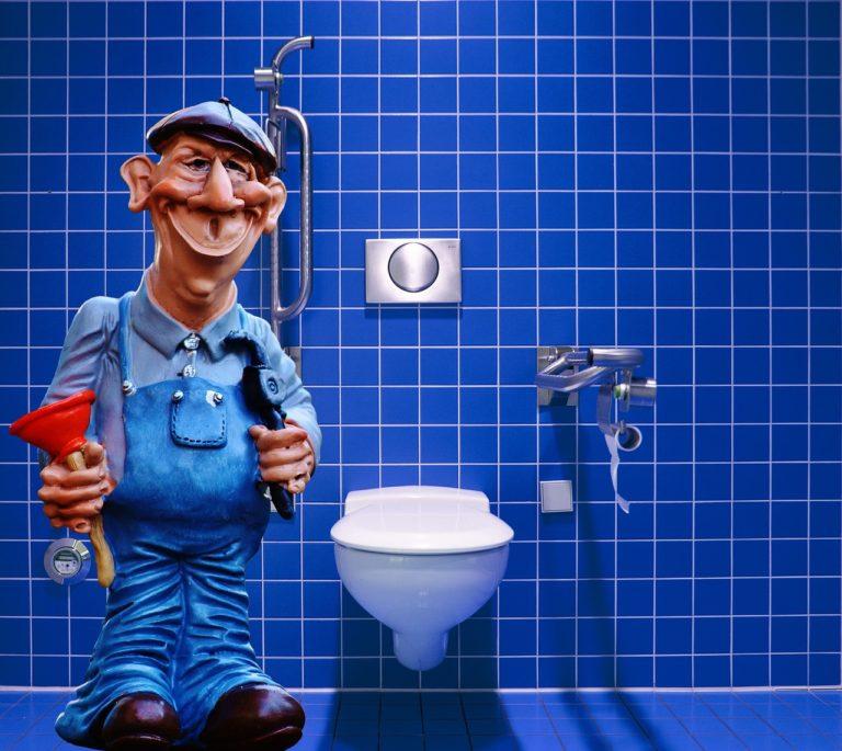 Ein blau gefliestes WC mit einem weißen WC Sitz und silberen Armaturen. Links neben dem WC steht eine Klempner- Figur mit einer roten Saugglocke in der Hand.