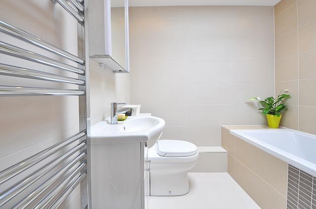 Ein hell gefliestes Bad mit einem Badheizkörper in Röhrenform am rechten Rand.