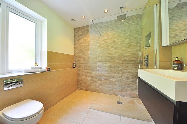 Es ist ein Bad mit Waschbecken, WC und einer bodengleichen Walk-In Dusche zu sehen