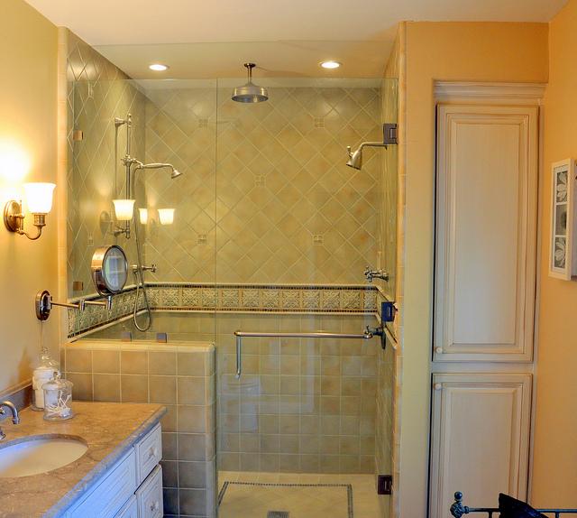 Ein helles Bad bei dem die Dusche mit einer Duschtrennwand aus Glas abgetrennt ist.