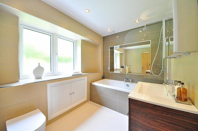 Ein helles, freundliches Bad mit Waschbecken , WC und Badewanne. Auf die Badewanne aufgesetzt befindet sich eine schicke Duschwand aus Glas