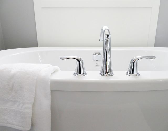 Blick auf eine Badewanne mit Badewannearmaturen. Über dem Rand hängt ein weißes Handtuch.