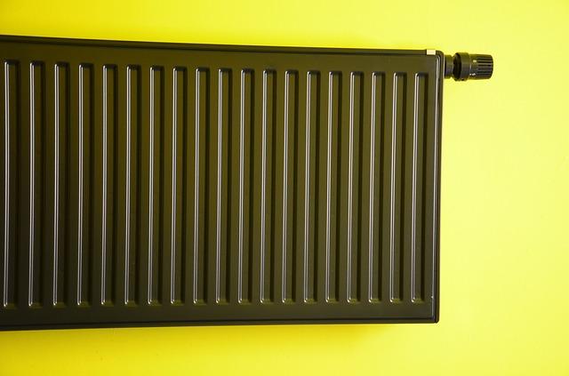 Ein schwarzer Kompaktheizkörper vor einer neongrüngelben Wand