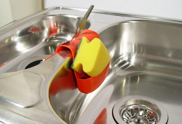 Eine silberne Küchenspüle mit zwei Spülbecken. In der Mitte der zwei Becken hängt darüber ein rotes Aufbewahrungsfach mit einem gelben Schwamm und einem silbernen Löffel darin.