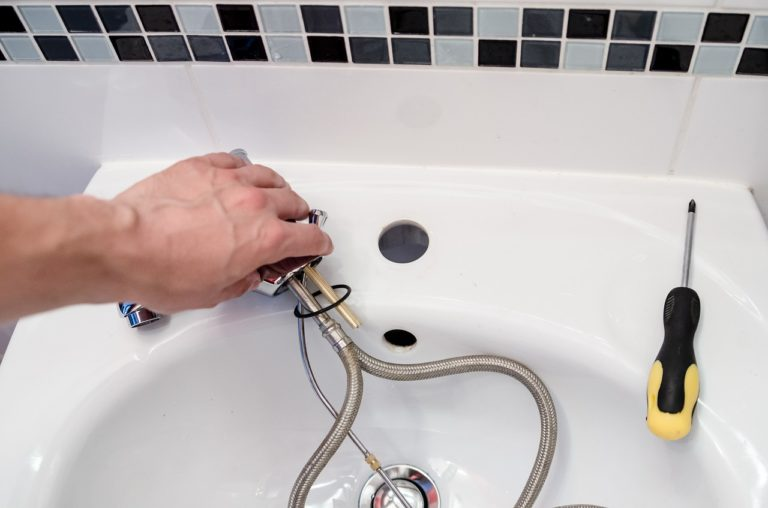 Eine Person hält eine Armatur in der Hand, während sie das Waschbecken montiert. Auf dem Rand liegt ein Schraubendreher.