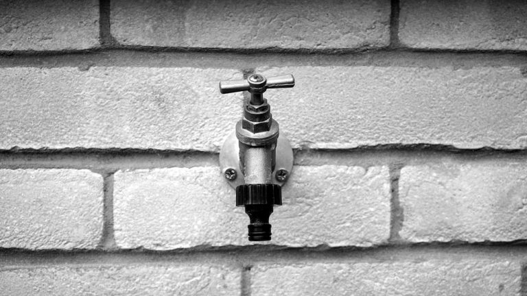 Ein schwarz-weiß Bild auf welchem man frontal einen silbernen Wasserhahn montiert an einer Ziegelwand sieht. Am Auslauf des Wasserhahnes ist ein schwarzes Gartenschlauch -Gewinde aus Plastik montiert. Der Wasserhahn hat einen Drehverschluss.