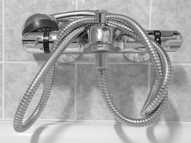 Ein Duschthermostat für die Wanne an der Wand mit aufgewickelter Brause
