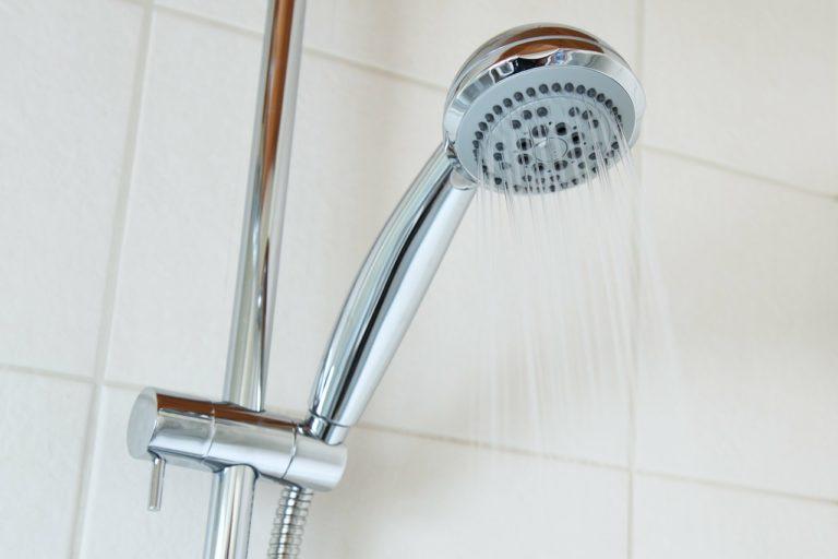 Eine silberne Dusch-brause bei der gerade das Wasser heraus läuft. Man sieht außerdem die silberne Duschstange und weiße Fliesen im Hintergrund.