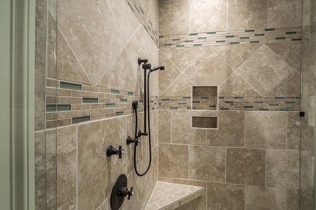 Eine Dusche mit einer Sitzbank ist mit beigen und gläsernen Fliesen ausgelegt. Die Glasduschwand ist offen und legt den Blick auf eine dunkle Duschstange und -kopf frei.