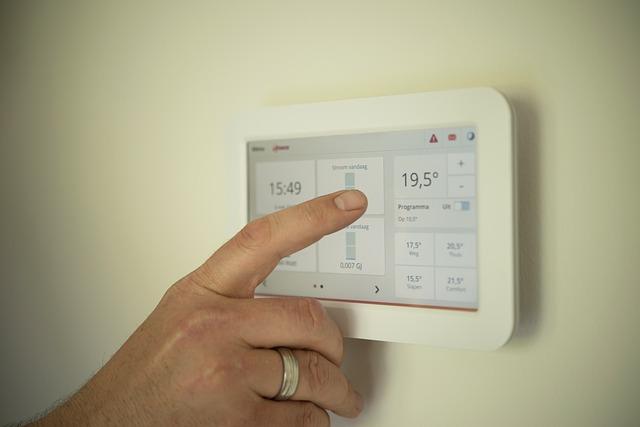 Eine Hand bedient ein Tablet an der Wand mit welcher die Heizungsregelung gesteuert wird.