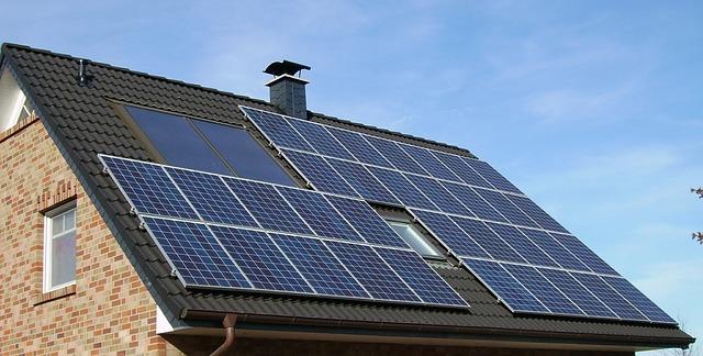 Ein Ziegelhaus mit schwarzem Dach ist mit einer Solaranlage ausgestattet.