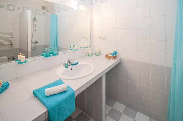 Ein weiß gefliestes Bad mit blauen Handtüchern und Kerzen geschmückt. An der Wand sieht man einen Spiegel, Lampen, Steckdosen und einen Schalter.