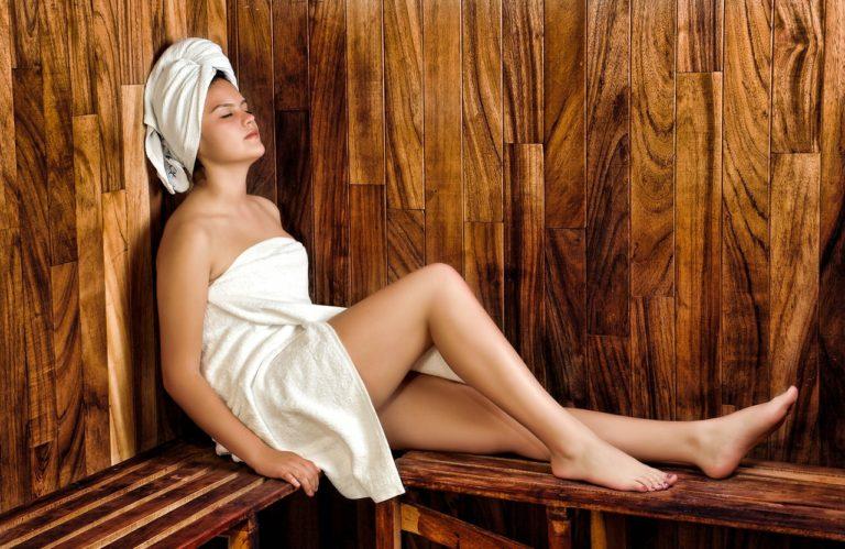 Eine attraktive Frau nur im Handtuch bekleidet, sitzt auf einer Holzbank in der Sauna. Auf dem Kopf trägt sie ein weißes Handtuch um die Haare.