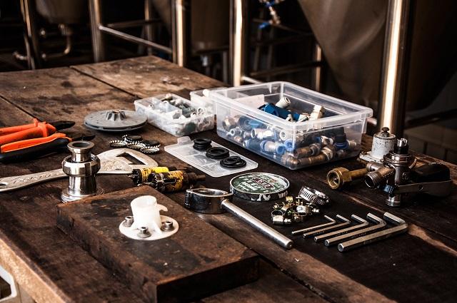 Werkzeuge für die Sanitärinstallation auf einer Werkbank liegend. Es sieht sehr rustikal und geordnet aus. Neben der Werkbank sind Metallrohre zu sehen.