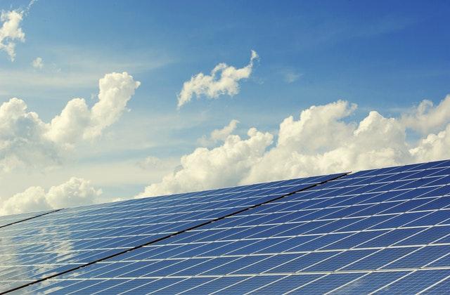 Vor einem blauen, leicht bewölkten Himmel liegt eine Solaranlage.
