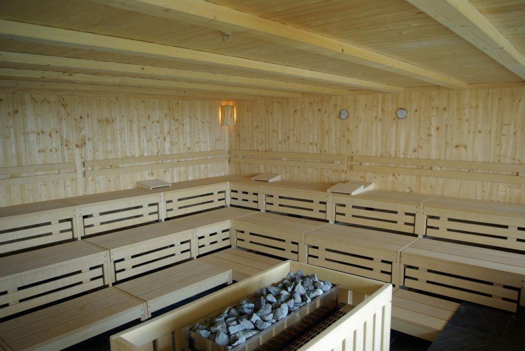 Eine Grßraumsauna mit drei Sitzreihen. In der Mitte befindet sich der Saunaofen mit Steinen darauf. Es ist überall schönes helles Holz und an der Wand befindet sich eine Lampe, ein Thermometer und ein Luftfeuchtigkeitsmesser.