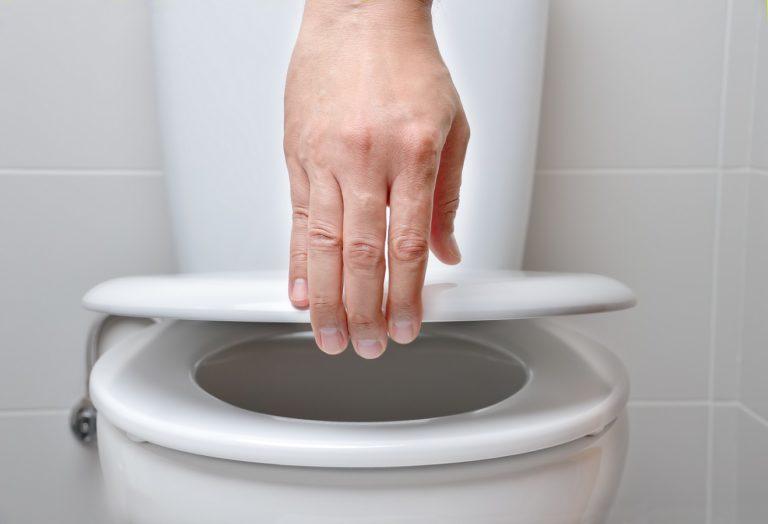 Eine Hand hält einen weißen WC-Deckel fest. Es schein kein Toilettendeckel mit Absenkautomatik zu sein.
