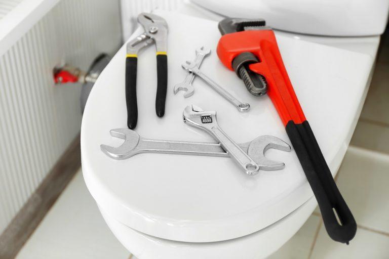 Auf einem geschlossenen, weißen Toilettensitz liegen verschiedene Werkzeuge verteilt.