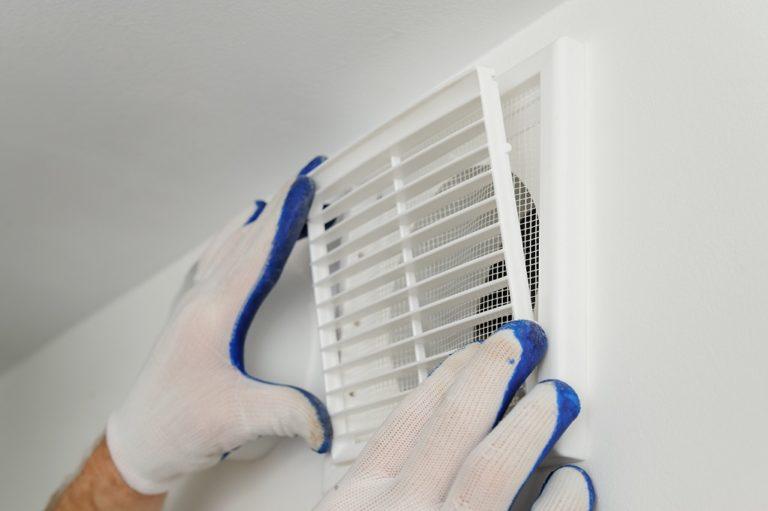 Zwei Hände mit weiß-blauen Handschuhen bekleidet setzen ein weißes Gitter vor eine Lüftung in der Wand.