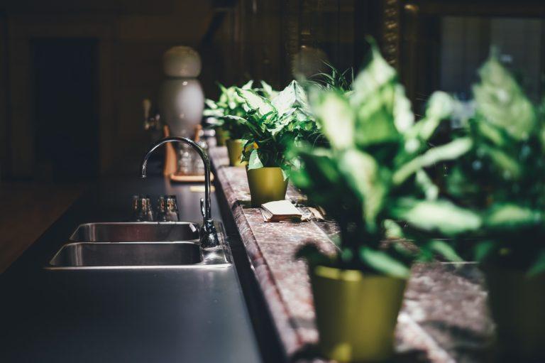 Man sieht eine dunkle Küchenzeile von der Seite in gedämpftem Licht. Auf einem Fensterbrett stehen Grünpflanzen in gelben Blumentöpfen. Im Hintergrund erkennt man einen Warmwasseraufbereiter.