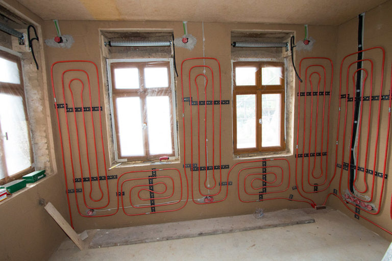 Ein Raum im Rohbau mit drei Fenstern. An der Wand wurden die roten Leitungen einer Wandheizung verlegt.