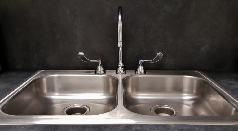 Eine silberne Küchenspüle mit zwei Spülbecken. In der Mitte der zwei Becken befindet sich ein Wasserhahn und links und rechts daneben sind der Kaltwasser sowie Warmwasser Regler. Umgeben ist die Spüle von einer Marmoroptik in dunklem Grau gehalten.