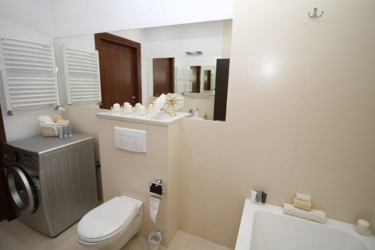 Ein in beige-weiß gehaltenes Badezimmer mit Blick direkt auf die weiße Toilette mit Unterputz WC-Spülkasten, den großen Wandspiegel sowie die silber-graue Waschmaschine. Es sieht edel aus und beinhaltet kleinere Design-Utensilien.