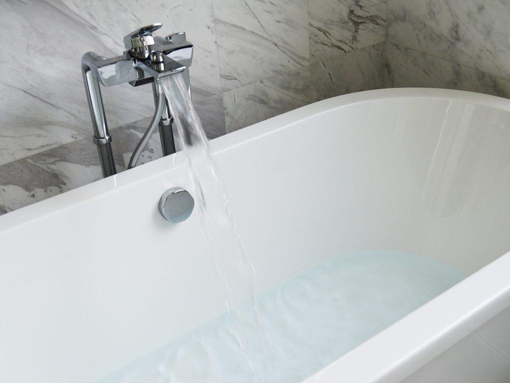 Eine Einhebel-Wannenarmatur ist zu sehen, aus der Wasser in eine weiße Badewanne einläuft.
