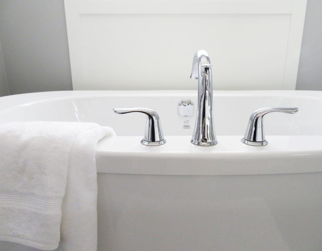 Man sieht eine Badewanne mit Wannenarmatur aus dem Rand. Ein weißes Handtuch liegt daneben.
