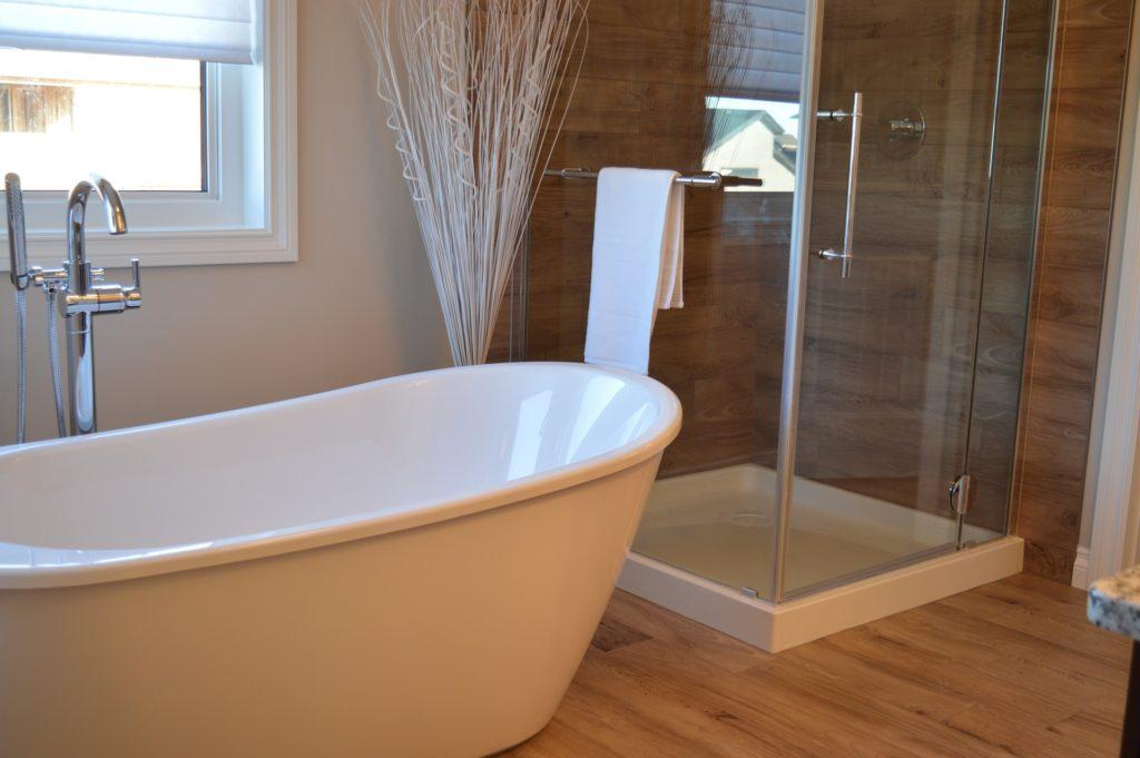 In einem modernen Bad samt Holz-Fußboden und -Vertäfelung an der Wand sieht man in der Ecke eine Duschkabine aus Glas stehen, daneben eine freistehende Badewanne samt Wannenarmatur aus dem Boden.