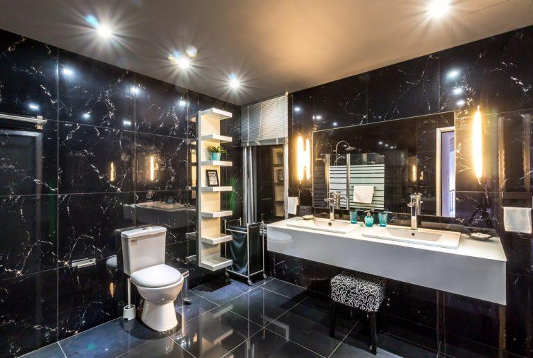 Man sieht ein dunkel gefliestes großes Badezimmer mit einem großen Spiegel und zwei Waschbecken. An der Decke gibt es Leuchtspots und links und rechts neben dem Spiegel sind weitere Badezimmerleuchten installiert.