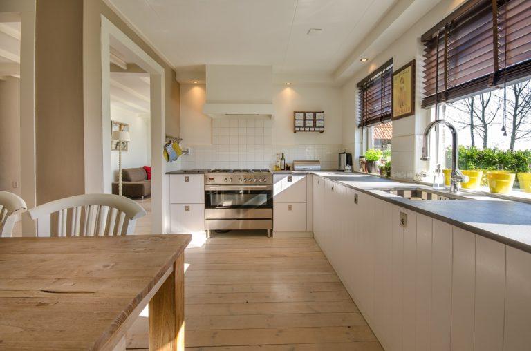 Eine schön helle, offene Küche. Farblich ist sie in Weiß und hellem Holz gehalten. Es gibt einen Holzdielenboden und auf der rechten Seite sieht man zwei große Fenster, durch welche man in den grünen Garten blicken kann.