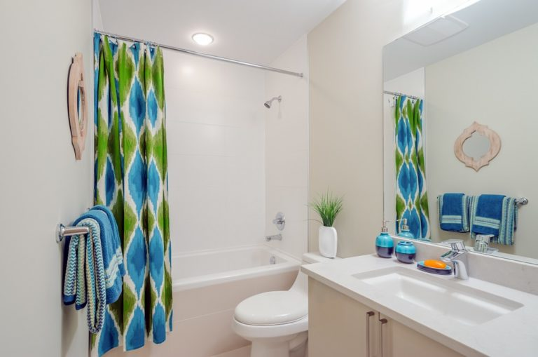 Ein Badezimmer mit weißen Wänden und einem grün-blauen Duschvorhang, der farblich heraussticht. Man sieht in dem Badezimmer ein Waschbecken, eine Toilette und eine Badewanne, wo der Vorhang seitlich davor hängt.