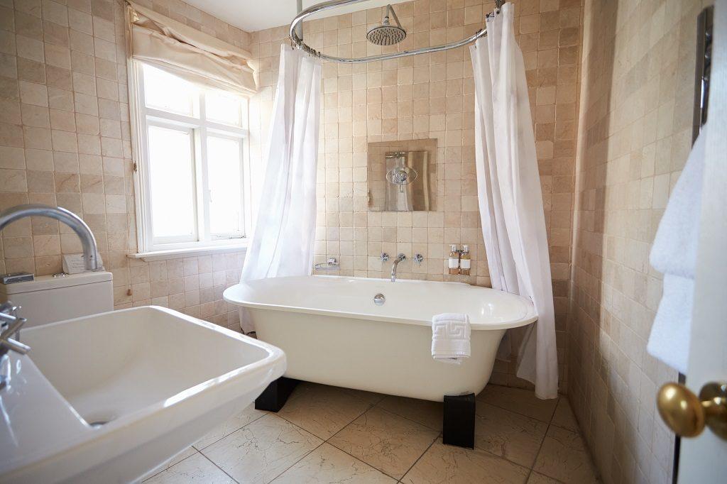 Eine freistehende Badewanne in einem beige gefliesten Badezimmer. Über der Badewanne hängt eine Duschvorhanghalterung mit einem weißen Vorhang. Es sieht alles edel und rustikal zugleich aus.