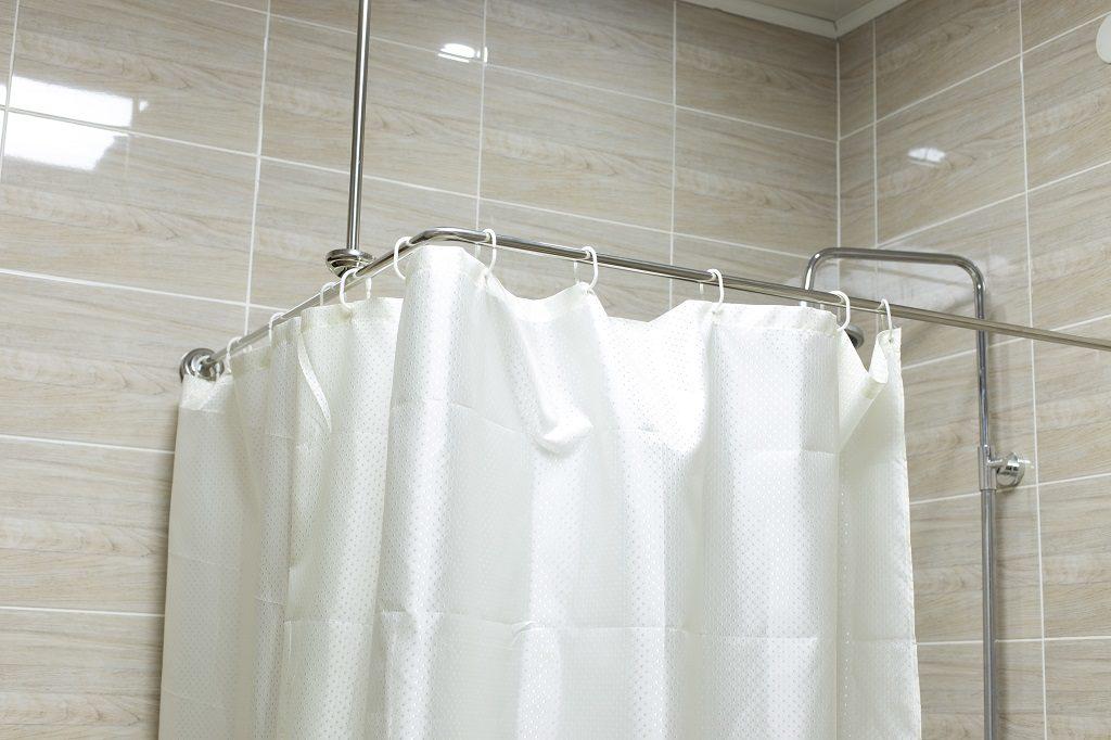 Ein weißer Duschvorhang, welcher mit einer Eckmontage an der Wand und Decke befestigt wurde. Die Fliesen dahinter haben eine helle beige Holzoptik.