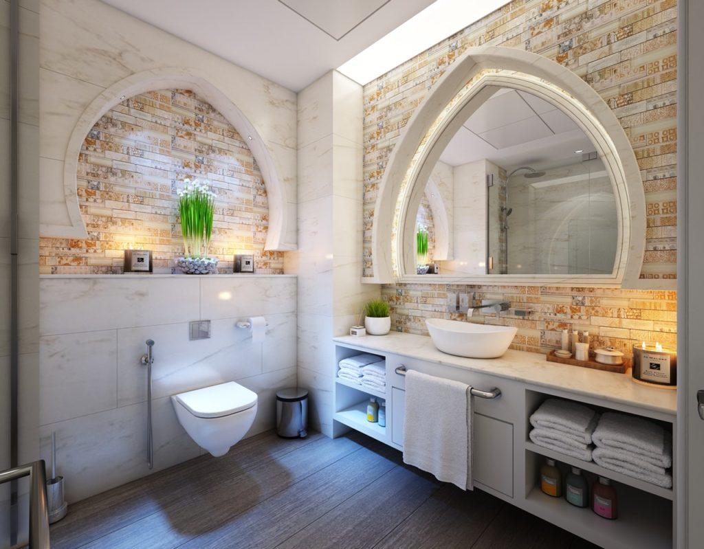 Ein sehr schönes Designbadezimmer. Man hat den Blick direkt auf das Waschbecken und die Toiilette. Es wurden hier einige Designelemente wie Kerzen, Pflanzen sowie kleine Aufbewahrungs- Möglichkeiten verwendet. Die Wände sind mit Marmor und in warm-bunter Ziegelstein Optik gefliest. Links neben der Toilette wurde ein unscheinbarer Haltegriff installiert.
