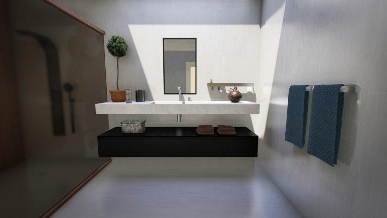 Ein Badezimmer mit Blick auf die Wasch-Armatur. Es gibt verschiedene Deko-Artikel wie eine kleine Kiste, eine Holzkugel oder ein kleines Bäumchen. An der rechten Seite gibt es einen Handtuchhalter mit blauen Handtüchern darauf.