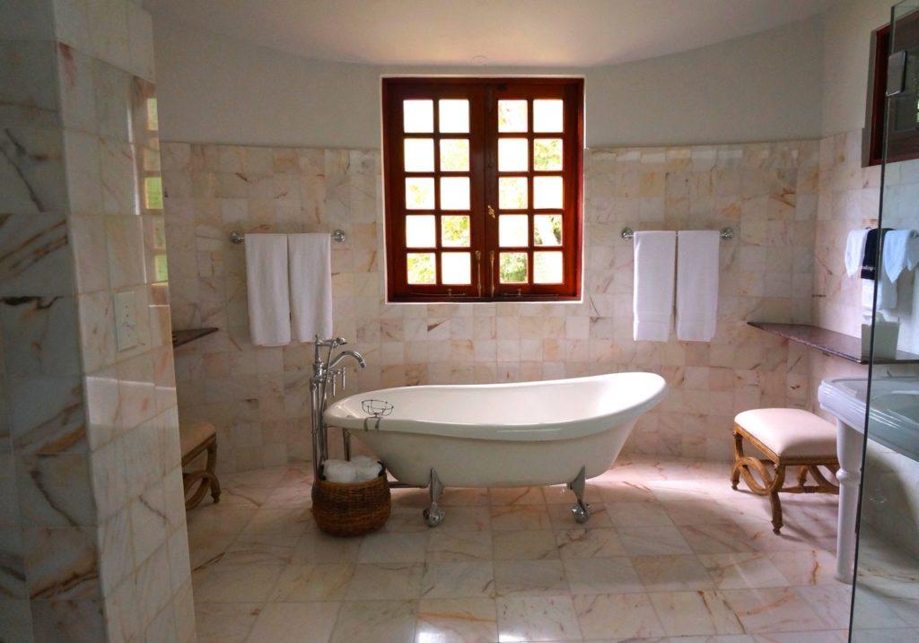 Man kann direkt in ein Badezimmer mit freistehender weißer Keramikbadewanne blicken. Dahinter befindet sich ein rotes Fenster mit vielen kleinen Glasscheiben. Links und rechts neben dem Fenster sind Handtuchhalter mit jeweils zwei weißen Handtüchern befestigt. Außerdem gibt es an den Rändern des Bades noch jeweils einen Hocher und neben der Wanne noch einen kleinen Korb.
