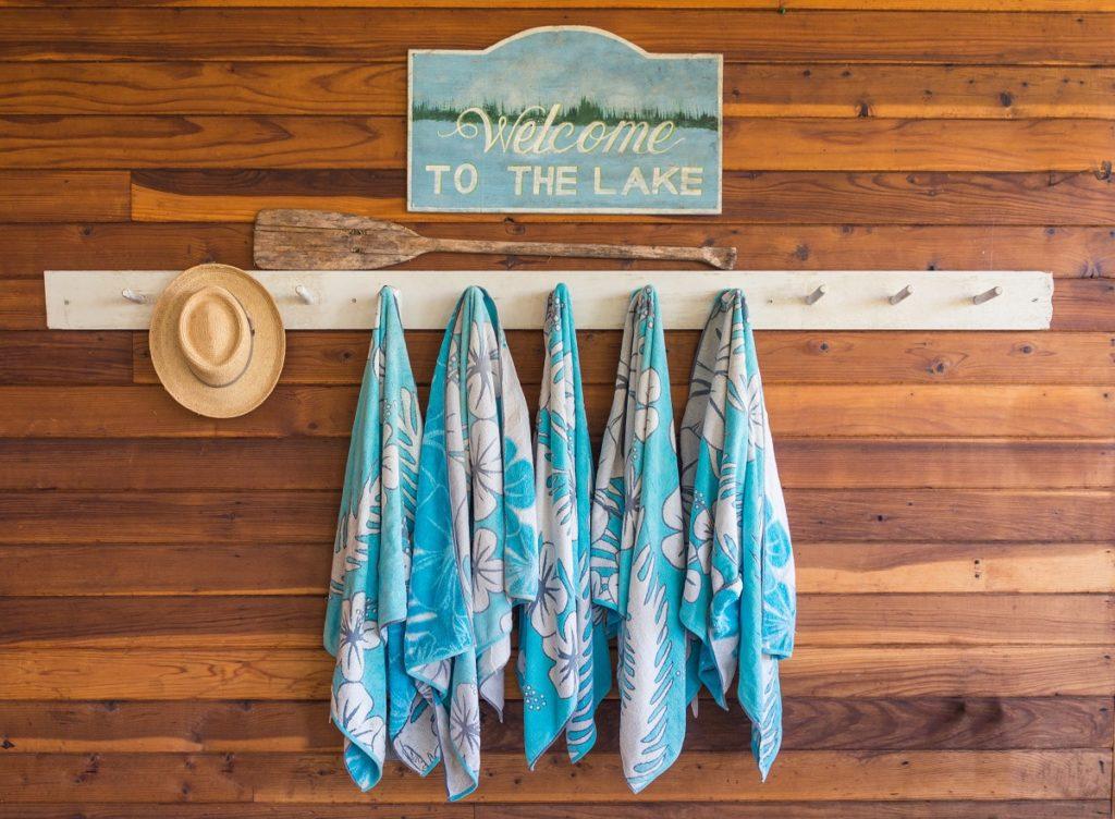 """Man sieht eine Wand mit braunen Holzdielen verkleidet. Daran befestigt ist ein Schild mit der Aufschrift """"Welcome to the Lake"""". Darunter befindet sich ein Handtuchhalter an dem fünf Badetücher und ein Hut hängen. Zwischen Schild und Handtuchhalter wurde ein Holzpaddel gehangen."""