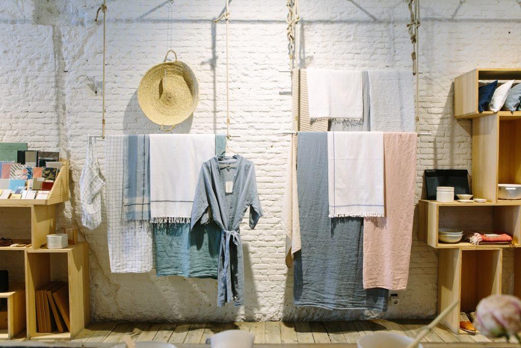 Man sieht verschiedene Tücher, Kleidung und Utensilien über Stangen gehangen, welche mit Seilen an der Decke befestigt sind. Die Wand dahinter ist eine weiß gestrichene Ziegelwand. Links und rechts neben den Tüchern sieht man Regale mit Kleinkram darin. Es wirkt alles sehr kreativ-rustikal.