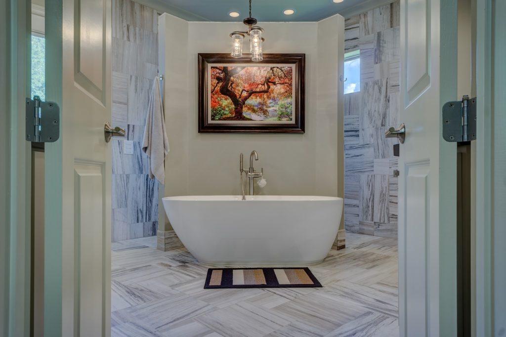 Durch zwei weiße Flügeltüren blickt man direkt auf eine freistehende weiße Badewanne. Darüber hängt ein buntes Bild eines Baumes und davor liegt ein gestreifter Badteppich. Das Bad ist in einer grauen Holzoptik gefliest.